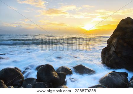 Ocean Tide Coming In Over The Rocks As The Morning Sunrises Over The Clouds