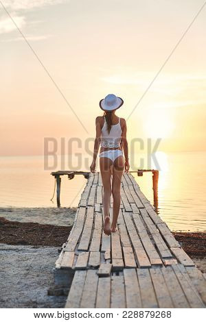 Beautiful Sexual Woman In White Hat And Bikini Stands On The Wooden Pier On The Beach Against The Se