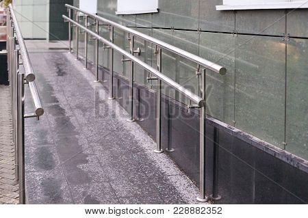 Long Ramp. Metal Smooth Handrails. Building Wall.