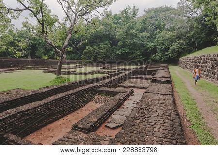 Sigiriya, Sri Lanka - Jan 9, 2018: Ruins Of Ancient Town Under Sigiriya Rock And Local Woman Walking