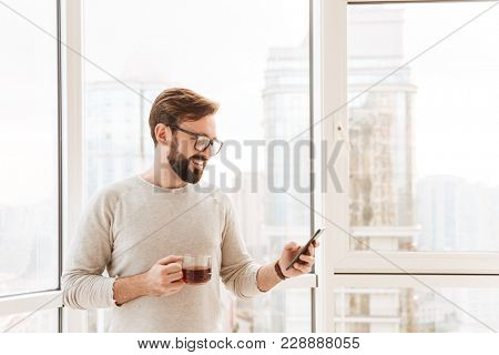 Portrait of a smiling man using mobile phone while standing at the window with cup of coffee at home