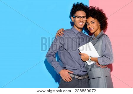 Young African Amercian Businesswoman Holding Tablet And Hugging Stylish Businessman On Pink And Blue