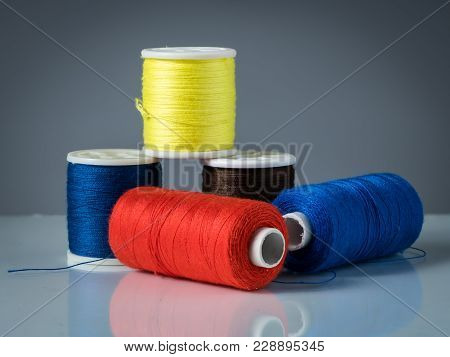 Spools Of Various Colored Threads For Knitting, Blue Red Yellow Black