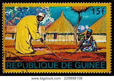 Moscow, Russia - February 27, 2018: Stamp Printed In Guinea Shows African Village, Man And Woman Are