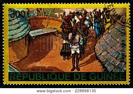Moscow, Russia - February 26, 2018: Stamp Printed In Guinea Shows A Scene Of Traditional Native Life