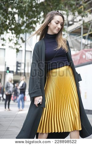 London, England - September 15, 2017 Beautiful And Stylish Girl In A Yellow Pleated Skirt And A Gree