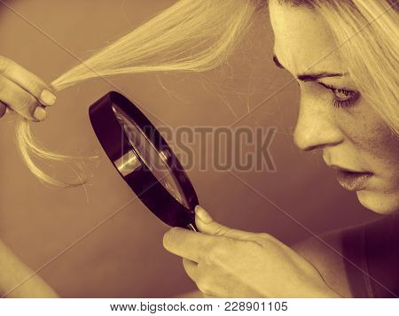 Haircare, Health Problem Concept. Unhappy Woman Looking At Ends Of Her Blonde Hair Through Magnifyin