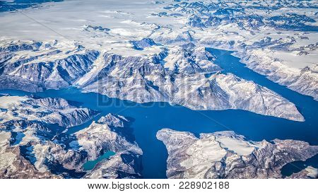Aerial Panoramic View Of Rugged Greenland Scenery Showing Glaciers, Icebergs And Mountain Ridges On