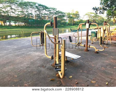 Outdoor fitness corner with exercise equipment in a park by the river.