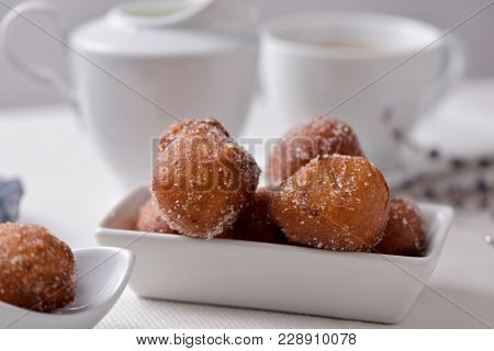 a white ceramic bowl with a pile of bunyols de Quaresma, typical pastries of Catalonia, Spain, eaten in Lent, on a table set with a white tablecloth