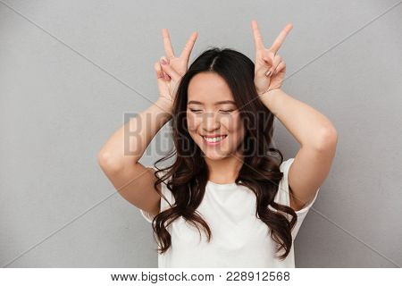 Portrait of amusing asian girl 20s in casual t-shirt having fun and showing peace sign with both hands from her head isolated over gray background
