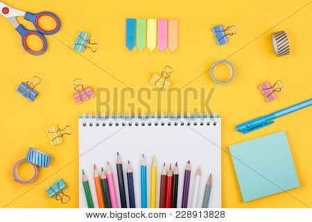 Multicolored Set Of Pencils And Blank Notepad And Office Supplies  Laying On Yellow Background Top V