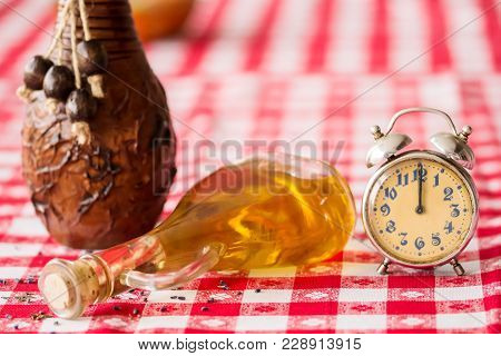 Beautiful Arrangement With An Old Analog Clock And A Bottle Of Oil Near A Vase