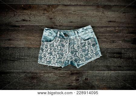 Denim Shorts On Wooden Shelf. Short Denim Shorts For Ladies. Vintage Shorts Openwork From New Collec