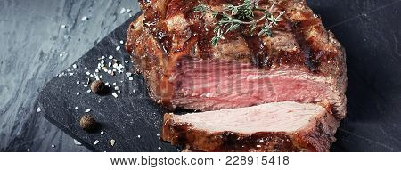 Banner Of Closeup Of Cut Medium Rare Roast Beef Steak With Herbs