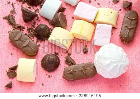 Different Sweets On Pink Background: Marshmallows, Zephyr And Chololate. Tasty Homemade Candies, Top