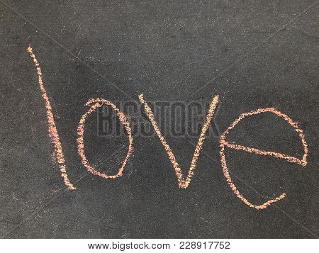 The Word Love, Written In Pink Sidewalk Chalk On A Sidewalk