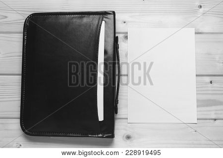 Black Leather Briefcase With Papers And Blank White Sheet Of Paper, Close-up Top View. Mock Up For T