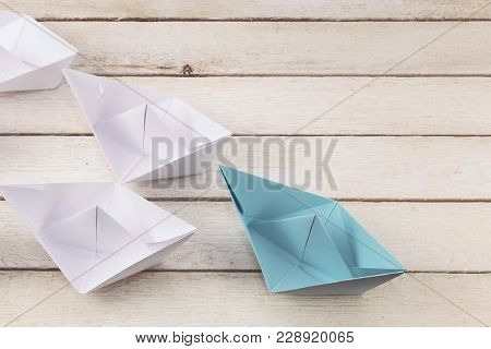 Leadership Concept With Paper Ship Leading Among White