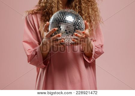 Close-up Of Disco Ball Is Mirror, Girl In Pink Dress With Curly Hair Is Holding Ball For Parties And