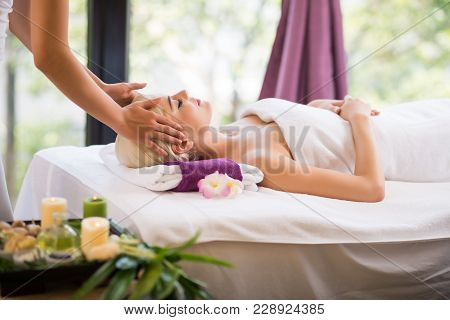 Pretty Young Woman Having Head Massage While Lying On Massage Table, Interior Of Luxurious Spa Salon