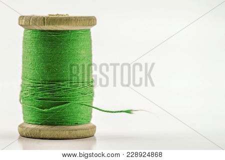 Reel Or Spool Of Green Sewing Thread Isolated On White. Shallow Depth Of Field. Close-up Macro Shot.