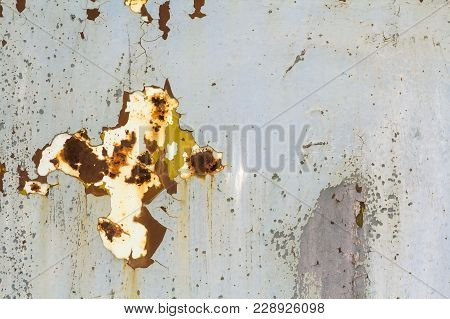 Abstract Background Texture Of Vertical Grungy Rusting Metal Plate With Peeling Paint And Extensive