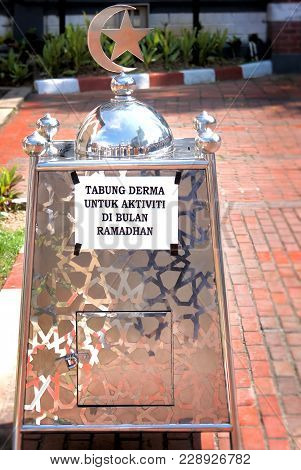 Large Silver-colored Container With Dome And Hilal For Donations And The Inscription In Malaysian La
