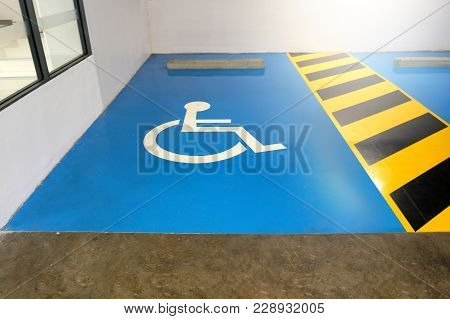 The Parking Space Is Available To For The Disabled. The Symbol Of The Disabled White On A Blue Backg