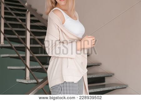 Young woman in stylish cardigan on stairs indoors