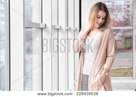Young woman in stylish cardigan near window indoors
