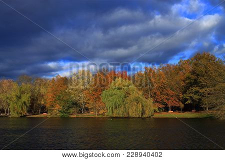 Lake And Storm Clouds Background - Heavy Dark Storm Clouds Over A Trees And Pond In A Park With The