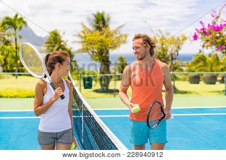 Tennis players friends having fun laughing playing on outdoor court. Couple or mixed double tennis partners outside in summer. Happy young people, woman and man living healthy active sport lifestyle.