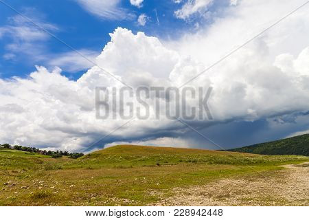 Hill With Green Grass And Dramatic Storm Clouds Overhead