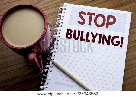 Hand writing text caption inspiration showing Stop Bullying. Business concept for Prevention Problem Bully written on note paper notepad on the wooden background with coffee and pen. poster