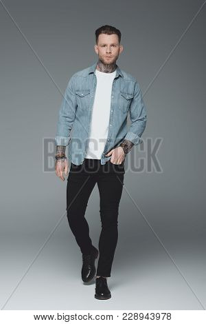 Full Length View Of Handsome Young Tattooed Man Walking With Hand In Pocket And Looking At Camera On