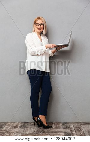 Full length image of Smiling middle-aged blonde woman in elegant clothes and eyeglasses posing sideways while holding laptop computer and looking at the camera over grey background