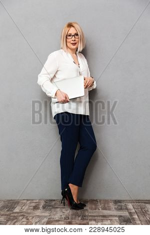 Full length image of middle-aged blonde woman in elegant clothes and eyeglasses holding laptop computer while posing sideways and looking at the camera over grey background