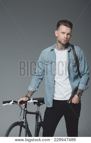 Handsome Young Man With Shoulder Bag And Bicycle Standing And Looking At Camera Isolated On Grey