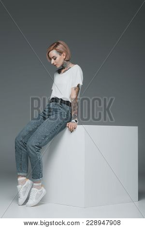 Beautiful Young Woman With Tattoos Sitting On Cube And Looking Down On Grey
