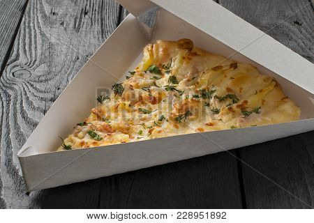 Slice Of Delicious Pizza In Box For Delivery On Dark Wooden Table. Pizza On Order. One Serving Of Pi