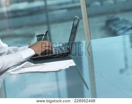 Saudi Man Hands Typing On Laptop At His Desk