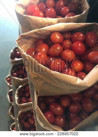 Bags of cherry tomatoes on a supermarket shelf