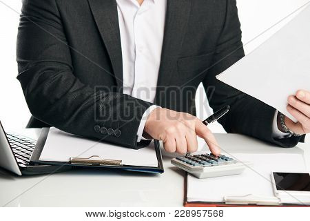 Close-up Of Financial Businessman Calculating Tax Expenses While Sitting At Office Over White Backgr