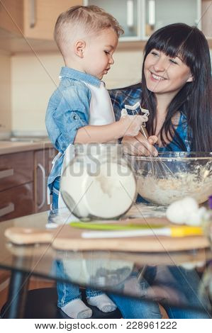 Mother Whisking Dough And Son Holding Dough Mold