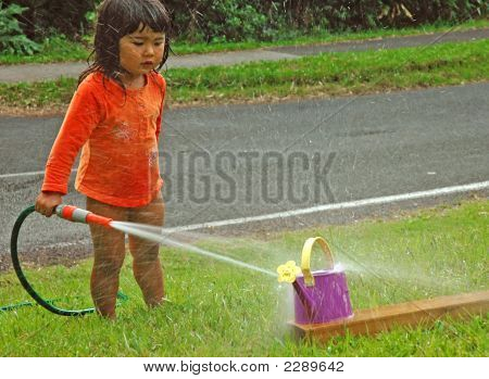 Little Girl Playing With Water In Summer Day.