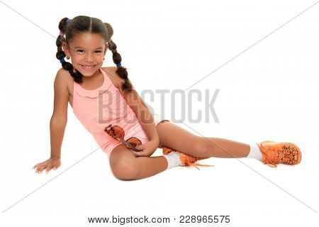Cute multiracial small girl laying on the floor and smiling - Isolated on white