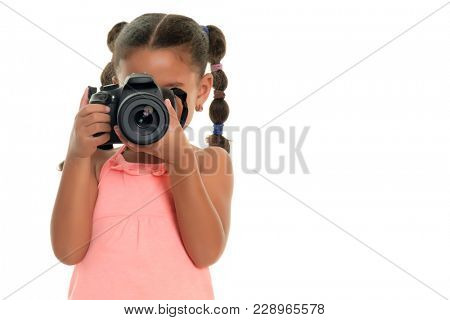 Small multiracial girl taking pictures with a professional camera - Isolated on white