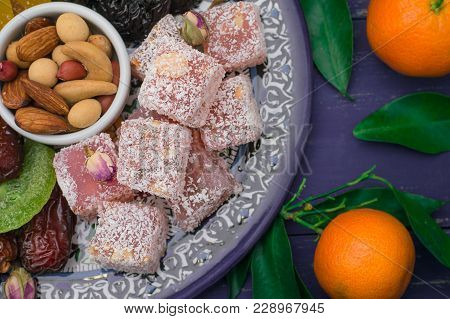 Set of eastern desserts. Marmalade, kivi, prunes, rahat lokum, nuts, mandarin, persimmon, dried apricots, pistachios, dates, raisins in a colorful blue plate Wooden rustic background Top view poster