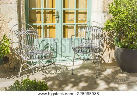 Vintage Wrought-iron Forged Chairs In The Garden